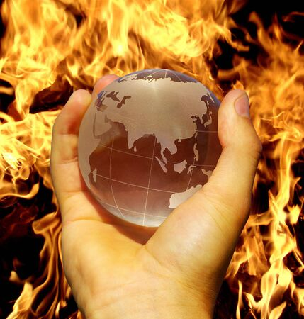 protection of land: globe in hand isplated on fire