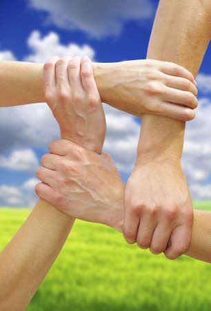 linked: Linked hands on a sky background symbolizing teamwork and friendship