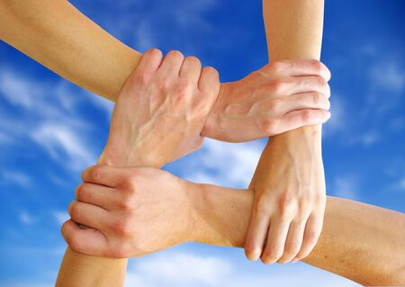 Linked hands on a sky background symbolizing teamwork and friendship photo