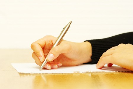 autograph: Pen in woman hand isolated on wood background Stock Photo