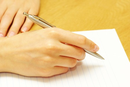 Pen in woman hand isolated on wood background photo