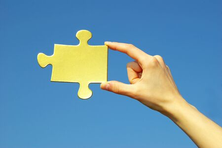 puzzle in hand isolated on blue background photo