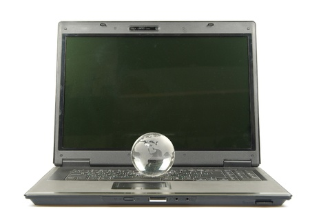 glass globe placed on a laptop isolated on white photo