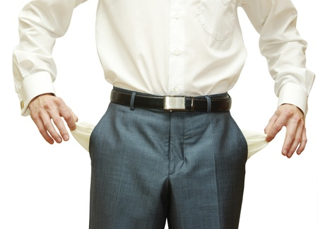 losing money: Businessman with empty pockets on white