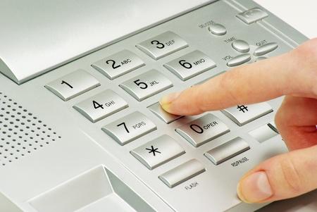 finger with  gray telephone keypad photo