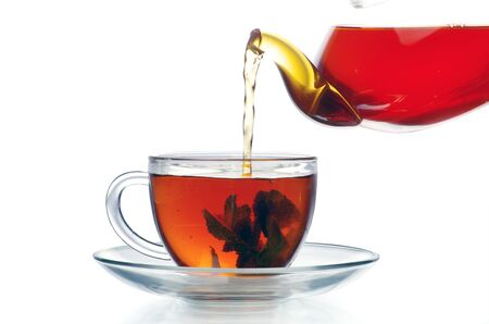 Tea being poured into glass tea cup photo