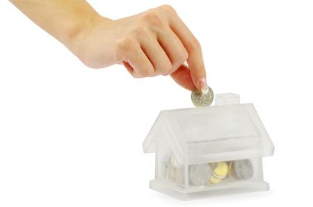cuenta bancaria: La mano con la moneda y el banco casa aislada en el fondo blanco Foto de archivo