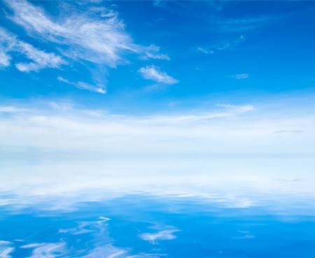 cielo y mar: nubes blancas mullidas con el arco iris en el cielo azul Foto de archivo