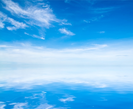cloudiness: white fluffy clouds with rainbow in the blue sky Stock Photo