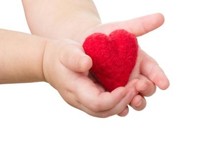 cuore nel le mani: Del bambino mani con un cuore rosso Archivio Fotografico