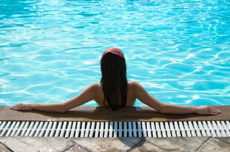 young woman sitting in swimming pool Stock Photo