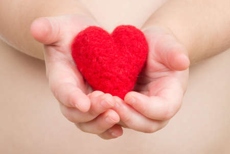 Childs hand with a red heart photo
