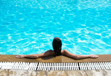 Portrait of young woman sitting in swimming pool photo
