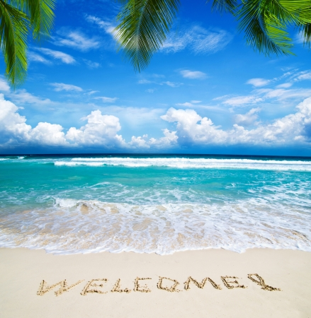 welcome written in a sandy tropical beach photo