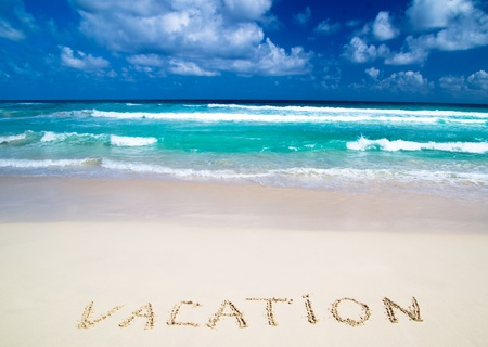 vacation written in a sandy tropical beach photo