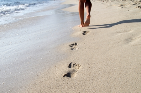 Footprints in wet sand of beach photo