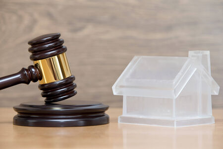 foreclosure: Closeup of a toy house model and a brown gavel