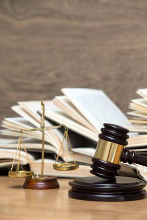 golden rule: Wooden gavel, golden scales of justice and books on wood background