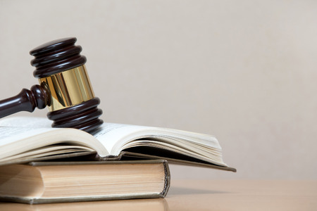 wooden gavel and books on wooden table photo