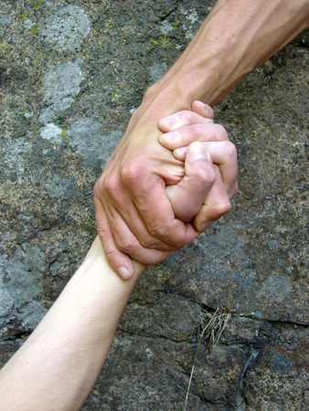 Hand in a hand on a background a rock