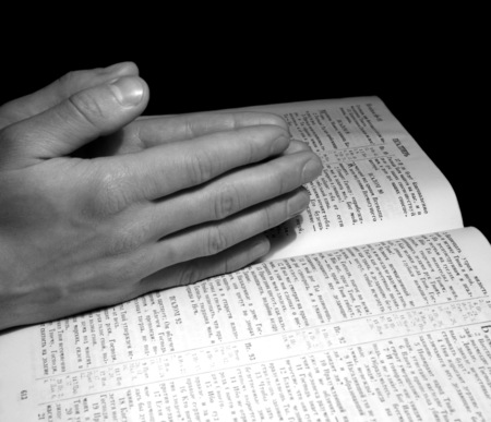 A mans hands clasped in prayer over a  Bible photo