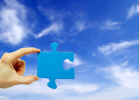 puzzle in hand isolated on sky background photo