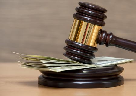 salarios: Mazo de la ley en una pila de dinero estadounidense