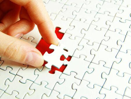 uniting: hands holding a puzzle piece . business concepts