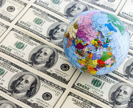 whiteness: A globe and dollars is isolated on a whiteness
