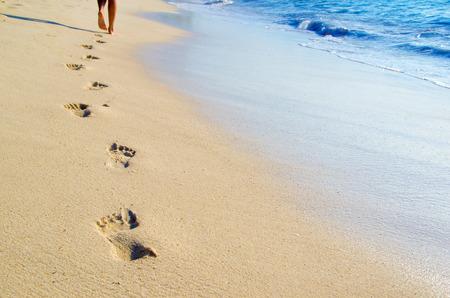 해변의 젖은 모래에 발자국 스톡 콘텐츠
