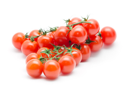 tomate cherry: los tomates con las hojas verdes aisladas sobre fondo blanco