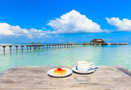 lunch table: A cup of tea on table with sea at the background Stock Photo