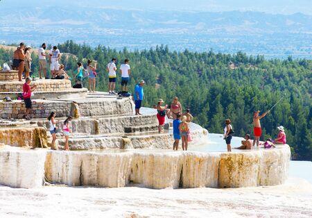 pamuk: Pamukkale, Turkey - August, 14 2015: Tourists on Pamukkale Travertine pools and terraces. Pamukkale is famous UNESCO world heritage site in Turkey Stock Photo