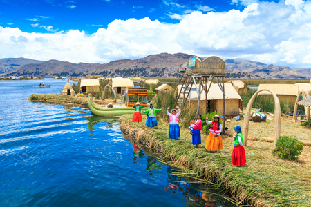 PERU - 11 MEI 2015: Niet-geïdentificeerde vrouwen in traditionele kleding verwelkomen toeristen in Uros-eiland