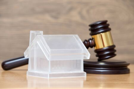 repossession: Closeup of a toy house model and a brown gavel