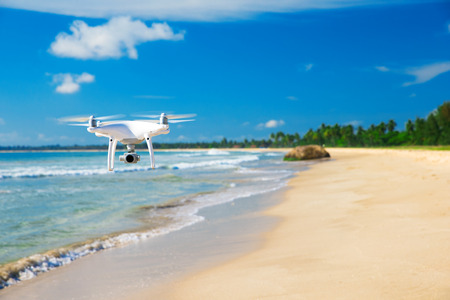 drones: drone flying over sea. white drone hovering in a bright blue sky. New technology in the aero photo shooting.