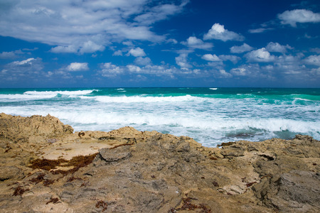 Sea waves crashing over rocks on wild stone beach in Mexico. Tropical sea relax Stock Photo