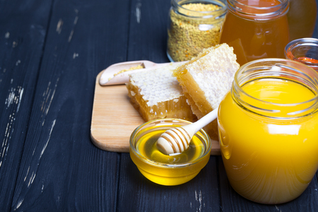 Honey in jar with honey dipper on wooden background