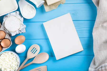 Dairy products on blue wooden table. Sour cream, milk, cheese, egg,  and butter. Top view with copy space