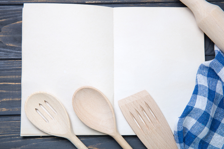 Kitchen utensil and notepad over wooden table background Stock Photo