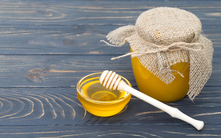 Honey with wooden honey dipper on wooden table Stock Photo