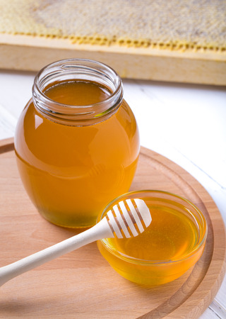 Honey background. Sweet honey in the glass jar . On wooden background.