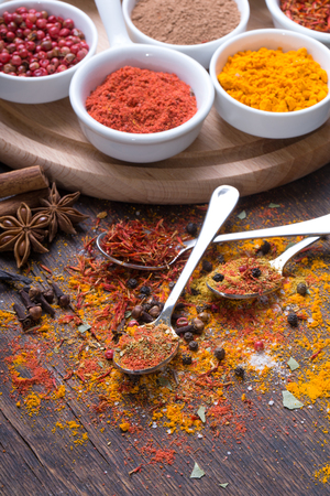 Colorful spices in spoons on dark wooden background, Top view