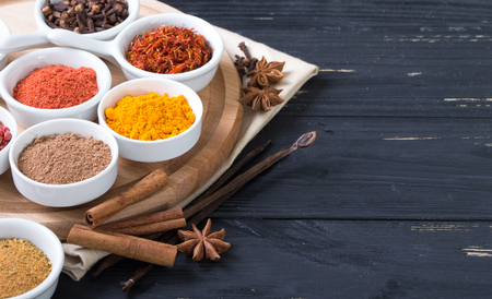 colorful spices in ceramic containers on a dark background Stock Photo