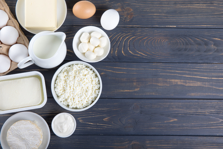 Dairy products on wooden table. Milk, cheese, egg, curd cheese and butter. Stock Photo