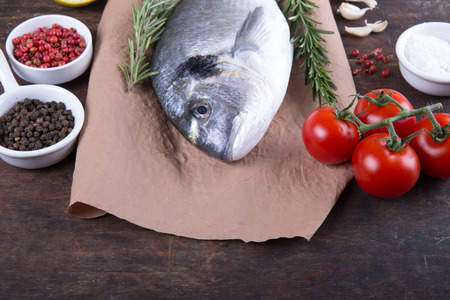 Raw fish dorado cooking and ingredients.  Dorado, lemon, tomato, herbs and spices. Top view on wood table