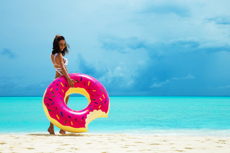 Woman with inflatable donut on the beach in summer sunny day. Summer vacation concept.