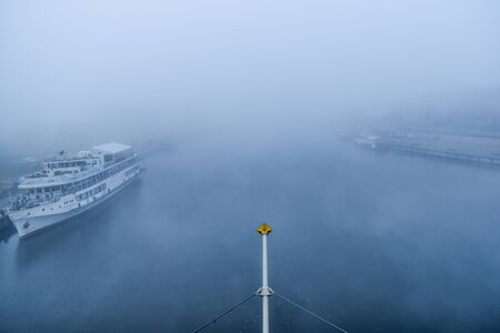 Two riverbanks and a ship during the fog