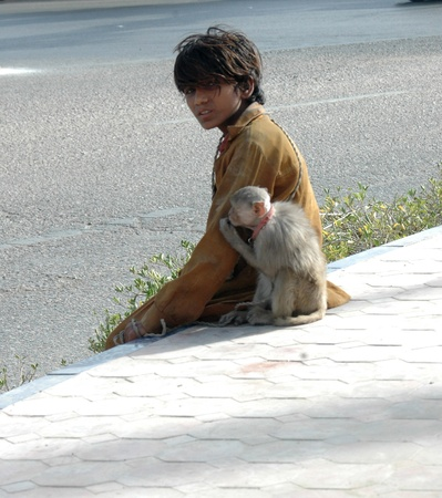 he is public: PAKISTAN_KARACHI_Young teen age boy monkey charmer he makes living to show monkey actin to public and money is sources to make living i Karachi 19 April 2012