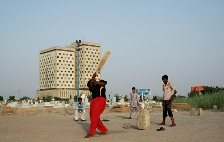bilding: PAKISTAN_ KKARACHI_pakistani children playing  cricket at christion garve yard {Gora Qabristan} in karachi.on may,03,2012